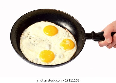 Hand holding a skillet with fried eggs isolated on white