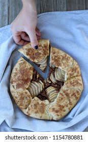 Hand holding a slice of pear and almond galette. Top view.