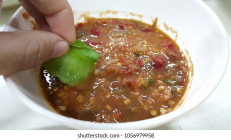 hand holding a slice of winged pea to dip into spicy shrimp paste dip.Thai local popular food.