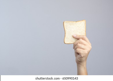 Hand holding sliced whole grain bread on white background