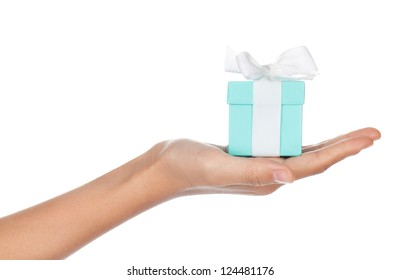 A hand holding a small blue box with a white ribbon in its palm isolated on white.