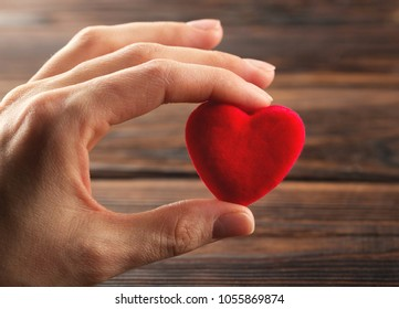 Hand holding small bright red heart on wood background