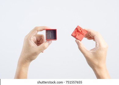 Hand holding small red gift box with ribbon and bow for special occasion on white background