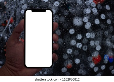 Hand holding smart phone with abstract rain drops on window with light bokeh in night urban background.