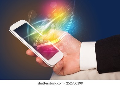 Hand holding smart phone with abstract glowing lines concept
