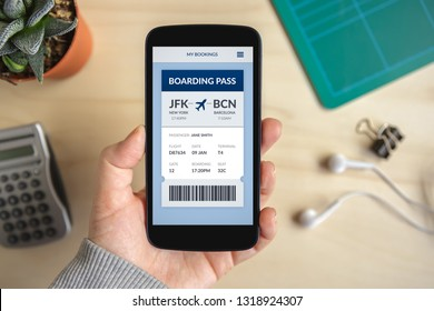 Hand holding smart phone with boarding pass concept on screen. Flat lay