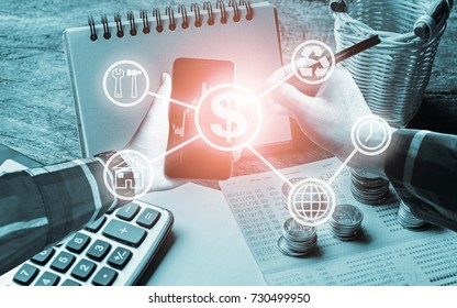 Hand holding smart phone with electronic pen and office tools, calculator,book bank,stack of coins, with business icons for finance management concept.