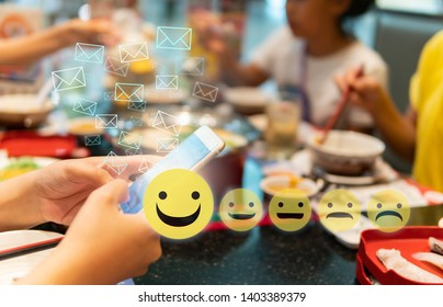 Hand holding smart phone with email icon and emoji emoticon over blur group eating in restaurant concept for  satisfaction responding