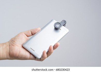 Hand holding smart phone equipped with extension lens on white background