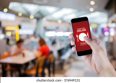 Hand holding smart phone with food order display on blur restaurant background