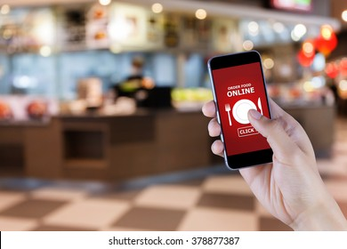 Hand holding smart phone with food order screen on blur of restaurant background