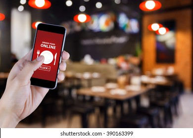 Hand holding smart phone with food order display on blurred of restaurant background
