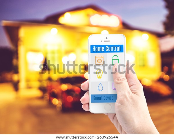 Hand holding smart phone with home control application with blur home background, Smart home concept