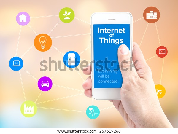 Hand holding smart phone with Internet of things (IoT) word and object icon and blur background, Digital Marketing concept.