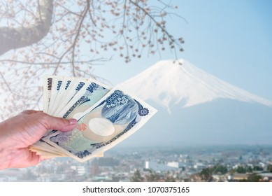 hand holding smart phone isolated on blurred Fuji mountain in Japan, travel insurance concept.
