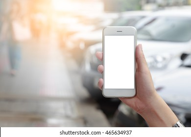 Hand holding smart phone isolated white screen with blurred urban people and white car parked on road