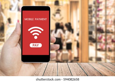 Hand holding smart phone with mobile payment on screen over blur people in the shopping mall background.