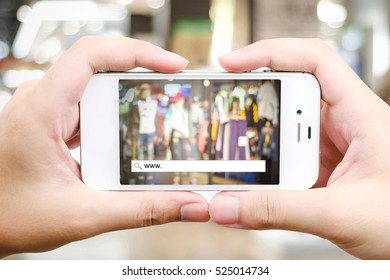 Hand holding smart phone with www. on search bar over blur store background, on line shopping ,business, E-commerce, technology and digital marketing background