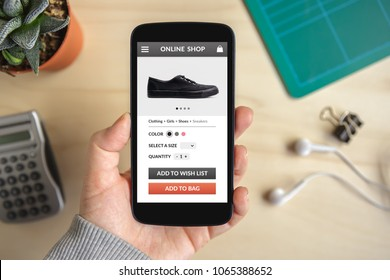 Hand holding smart phone with online shop concept on screen. screen content is designed by me. Flat lay