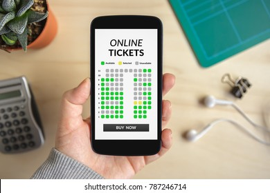 Hand holding smart phone with online tickets concept on screen. All screen content is designed by me. Flat lay