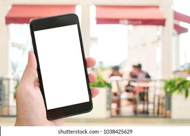 Hand holding smart phone over blur restaurant background, mock up, template, restaurant reservation, food online, food delivery concept