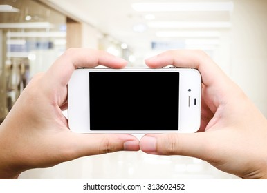 Hand holding smart phone over blur store background, e-commerce, smart pay, business and technology concept