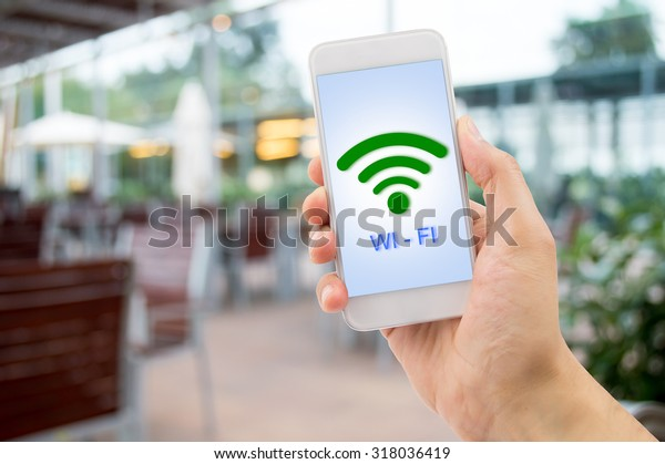 hand holding the smart phone searching the wifi signal at the terrace of bar