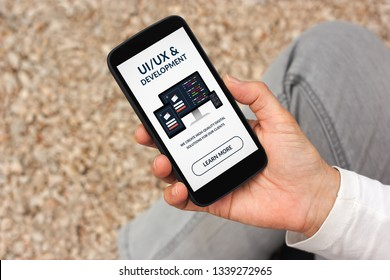 Hand holding smart phone with UI/UX design and development concept on screen.