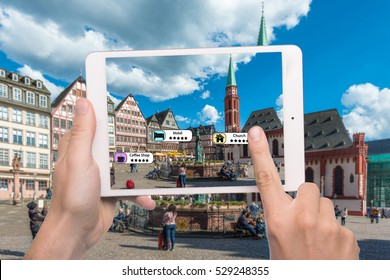 Hand holding smart phone use AR application to check relevant information about the spaces around customer. Frankfurt City in background. Augmented reality marketing concept