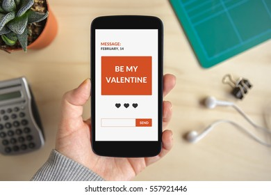 Hand holding smart phone with valentine's day concept on screen. All screen content is designed by me. Flat lay
