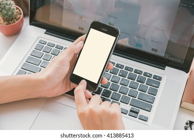 hand holding smart phone with white screen on desk office.