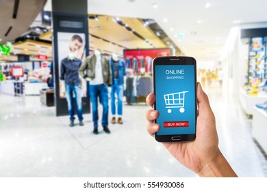 hand holding smartphone against blur bokeh of shop background with word online shopping buy now