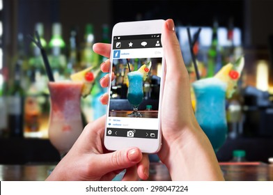 Hand holding smartphone against close up on mouth watering cocktails