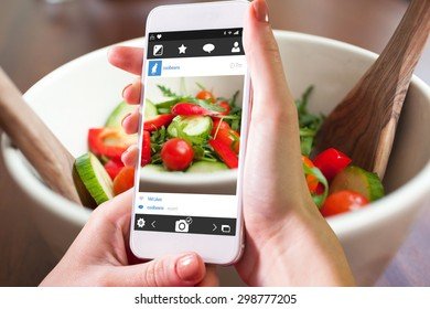 Hand holding smartphone against close up of a garden salad