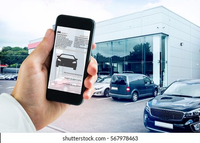hand holding smartphone against outside view of car dealership