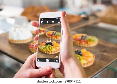 Hand holding smartphone against tray of sweet pastry tarts