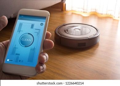 Hand holding smartphone with application control robot vacuum cleaner on screen mobile phone.Smart life technology concepts ideas