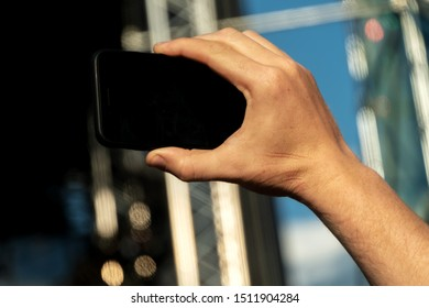 Hand holding a smartphone with a black screen and takes a close-up of what is happening