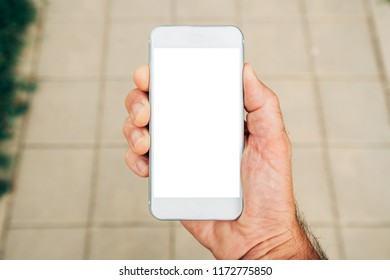 Hand holding smartphone with blank mock up screen on street, man using mobile phone device outdoor in urban surrounding