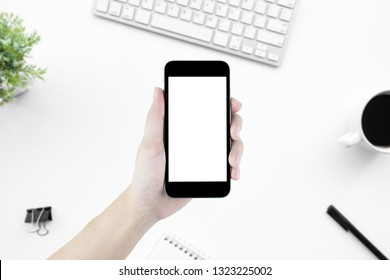 Hand holding smartphone with blank mock up screen over white office desk table. Top view image.