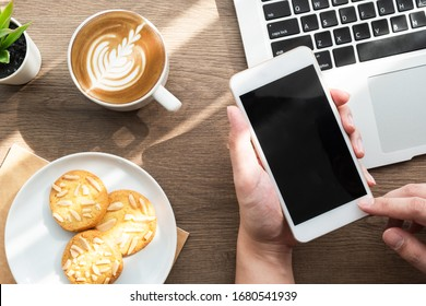 Hand holding smartphone with blank mock up screen over wood office desk table with cookies, cup of coffee and supplies. Top view, flat lay.