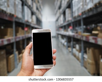 hand holding smartphone with blank screen in warehouse. E-commerce online shopping Concept.