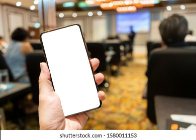 Hand holding the smartphone with blank screen on blurred image of people in conference room for meeting seminar as background. White screen in smart phone with clipping path.