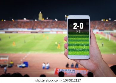 Hand holding smartphone with blur football field background.