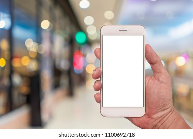 Hand holding smartphone with blur interior in shopping mall for background.