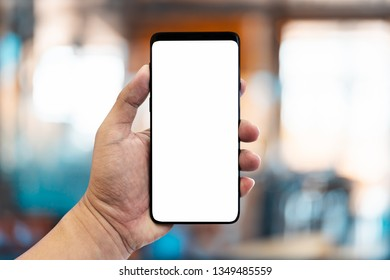 Hand holding smartphone with blur interior in cafe or coffee shop.
