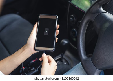 Hand holding smartphone and changing phone battery in car