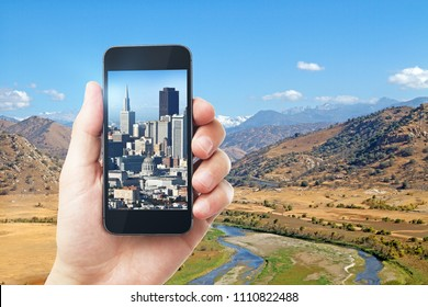 Hand holding smartphone with city on screen on creative outdoor wallpaper with sunlight. Photgraphy concept