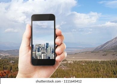 Hand holding smartphone with city on screen on creative outdoor texture with sunlight. Photgraphy concept