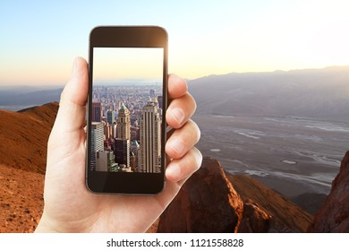 Hand holding smartphone with city on screen on creative outdoor background with sunlight. Photgraphy concept